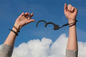 Hands breaking free of handcuffs.